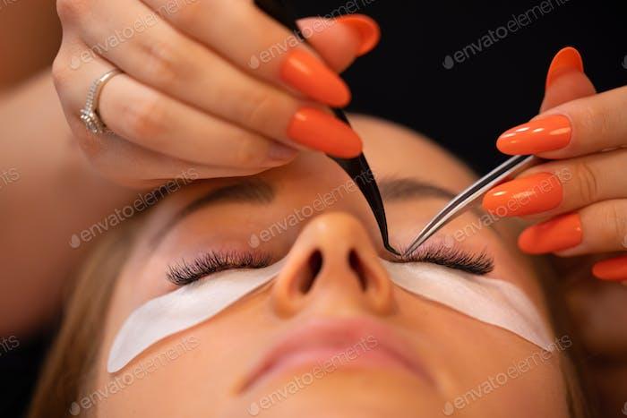 Hands Of Beauty Specialist Using Tweezers On Female Client