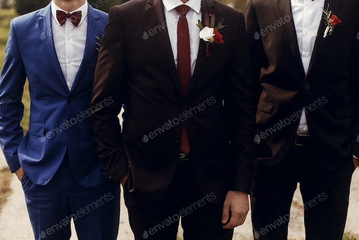 stylish groom with groomsmen in suits with boutonniere posing