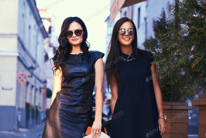 Two sexy brunette wearing stylish black dresses in sunglasses, posing near a terrace cafe in a city.
