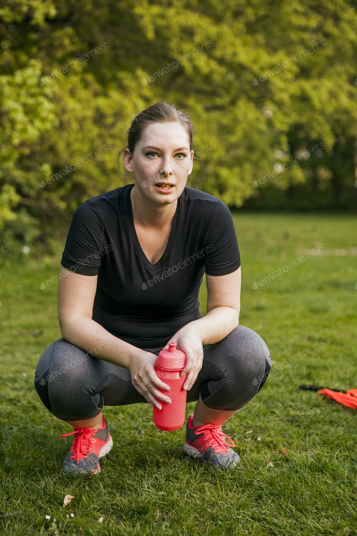 Portrait of sporty woman holding water bottle while crouching on grassy field at park