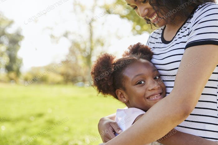 Portrait Of Mother Hugging Daughter In Park