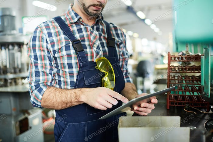 Unrecognizable Factory Worker Using Tablet