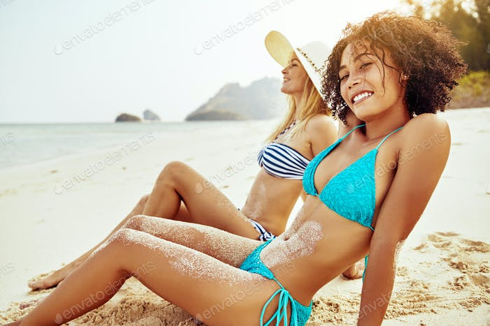Smiling friends in bikinis relaxing on a sandy tropical beach