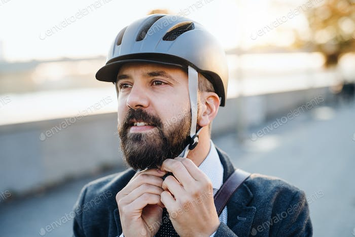 Businessman commuter traveling home from work in city, putting on a bicycle helmet.