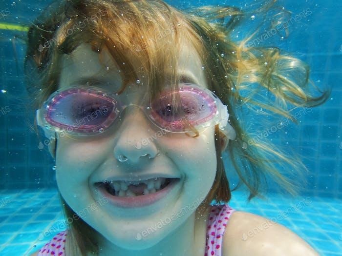 Closeup of caucasian girl underwater in the pool