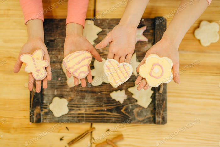 Little girls cooks hands holds cookies over board