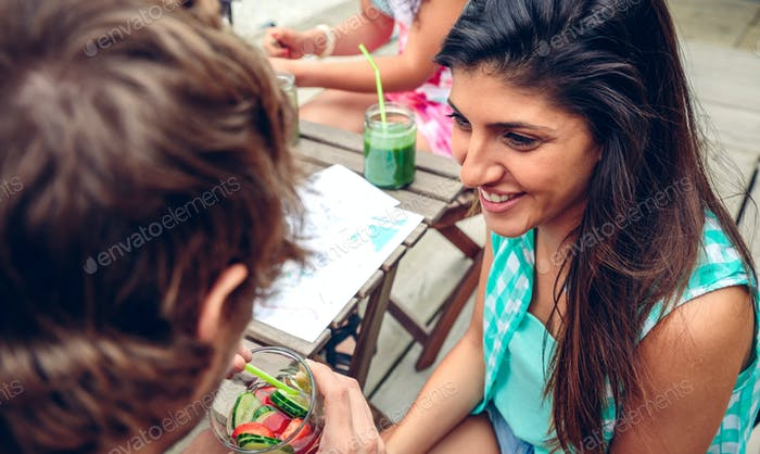 Smiling woman looking man drinking infused water cocktail