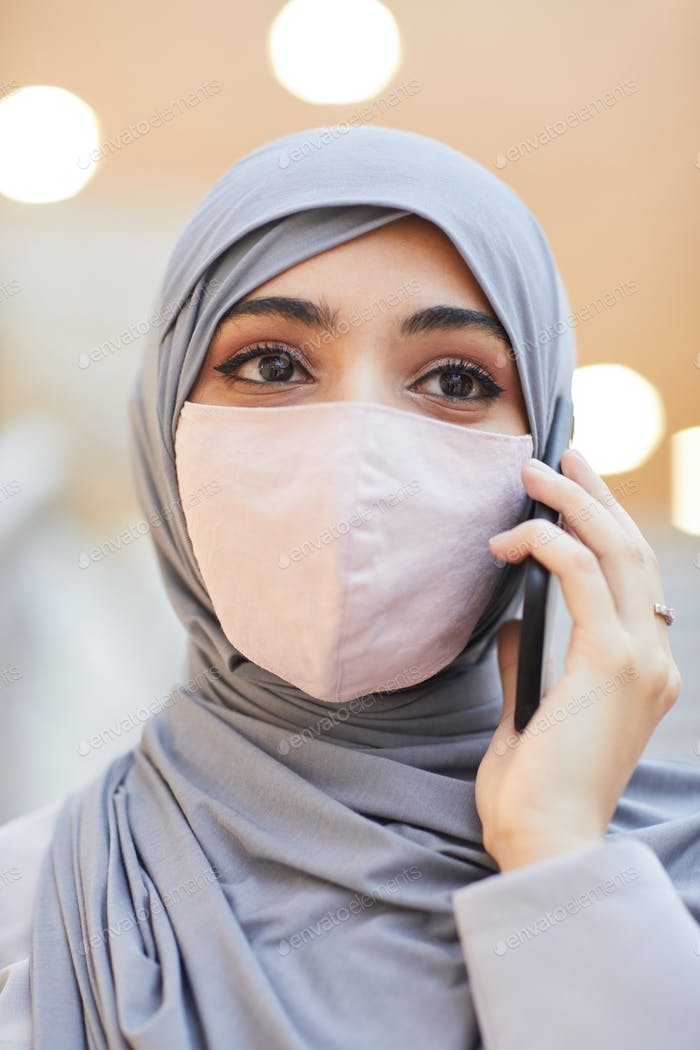 Middle-Eastern Woman Wearing Mask and Speaking by Smartphone