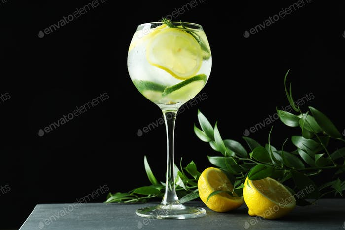 Glass of cocktail with citrus on dark background