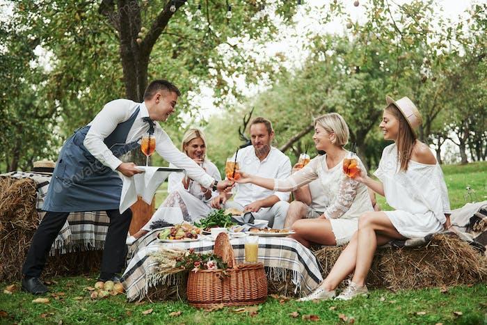 Sogar Kellner haben eine gute Zeit während des Gottesdienstes mit dieser schönen Gruppe von Freunden