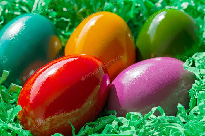 Colorful dyed Easter eggs in a green paper nest, group of Paschal eggs