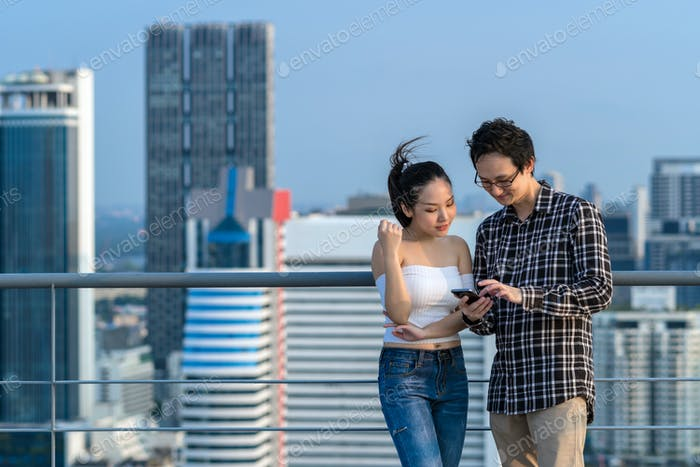 Couple colleague businessman and woman in casual suit are using smart mobile phone