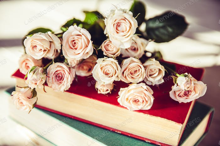 gentle roses with old books on a wooden background