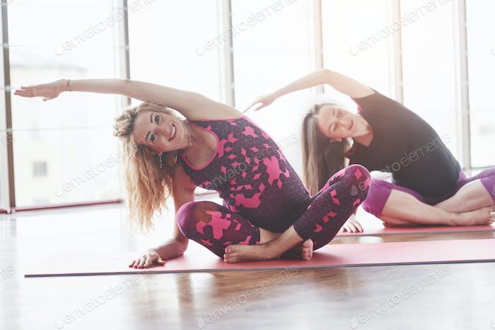 Konzept der Fitness und eines gesunden Lebensstils Zwei lächelnde schwangere Frauen haben einen Zug in der Halle