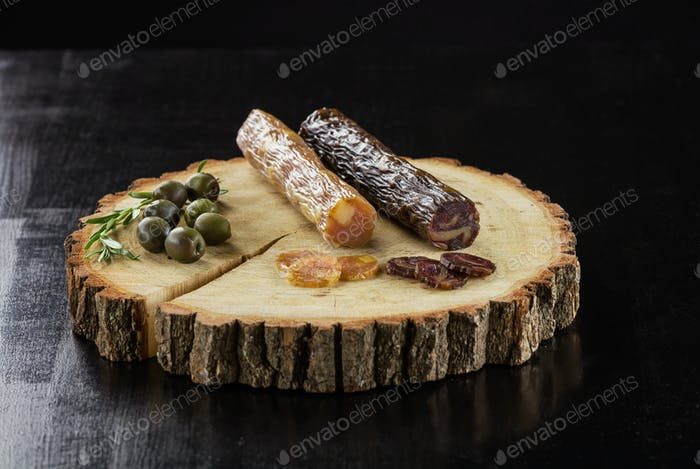 Smoked sausages and olives on wooden board over black