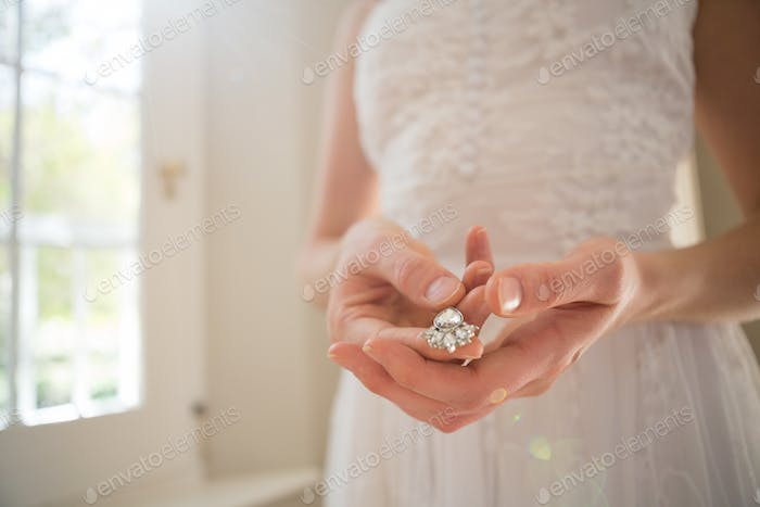 Midsection of bride holding diamond earring at home