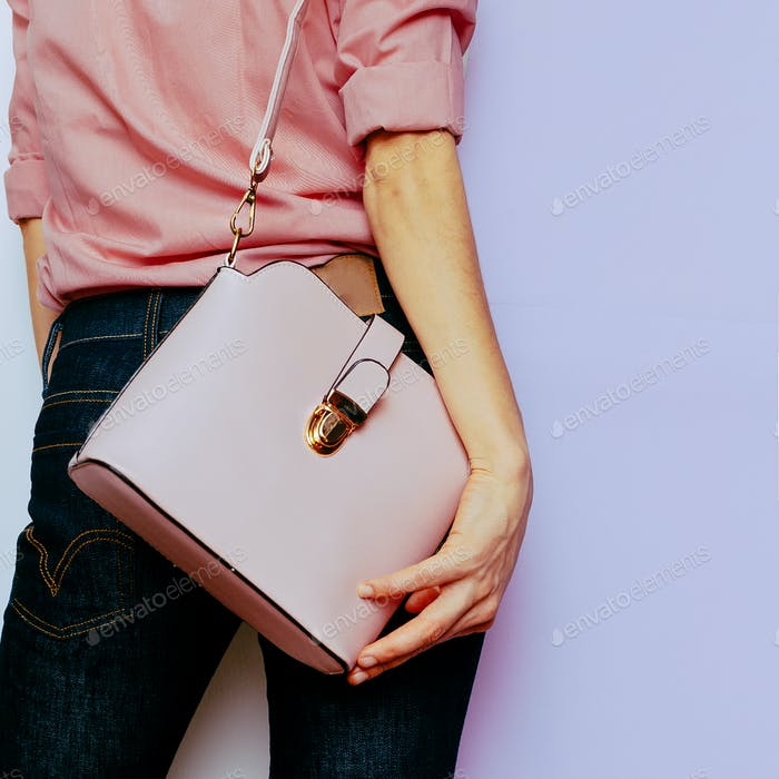 Girl in pink shirt and pink accessories. Bag and Stylish Jeans