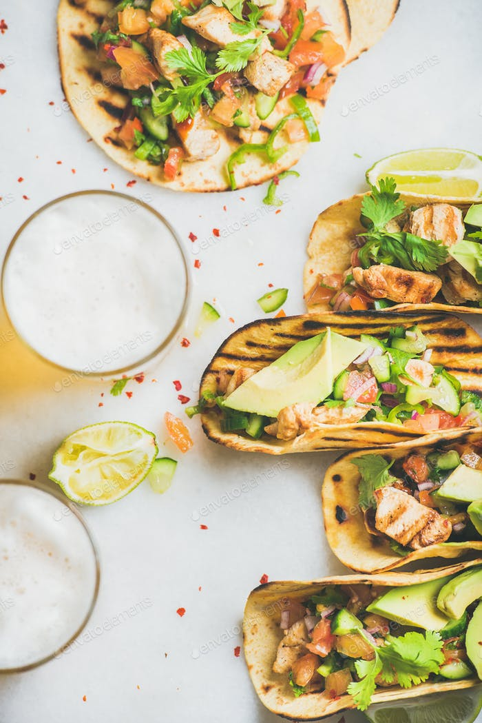 Healthy corn tortillas with chicken, vegetables, beer on grey background
