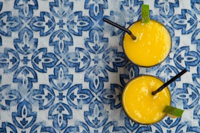 Frische tropische Früchte Smoothie Mango Saft auf blauem Hintergrund. Leerzeichen kopieren. Draufsicht.