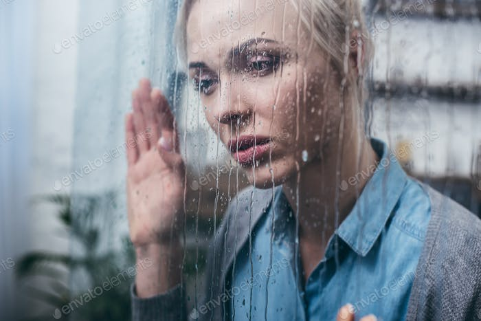 depressed adult woman touching window with raindrops