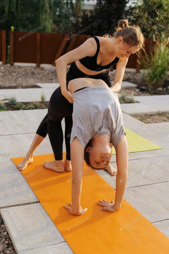 Zwei junge Mädchen üben Stretching und Yoga Training zusammen