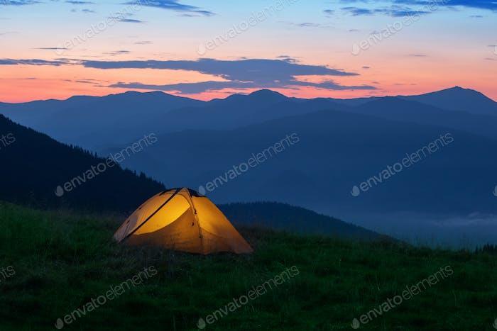 Orange tourist tent illuminated from inside on mountain