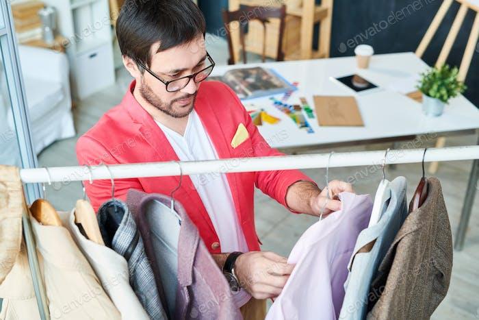 Designer exploring clothes on hangers