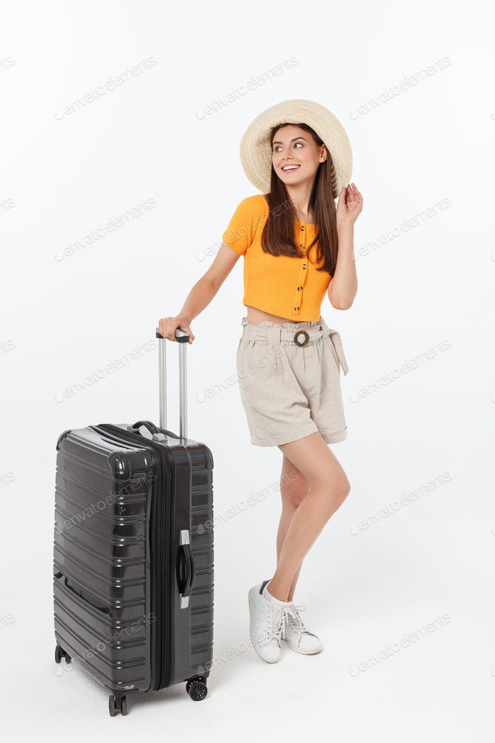 Woman tourist. Full length happy young woman standing with suitcase with exciting gesturing