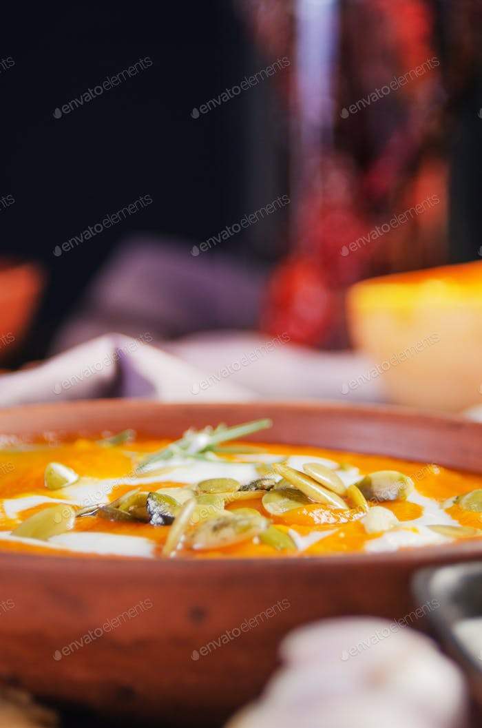 Homemade rustic pumpkin soup with seeds in clay dish on kitchen table