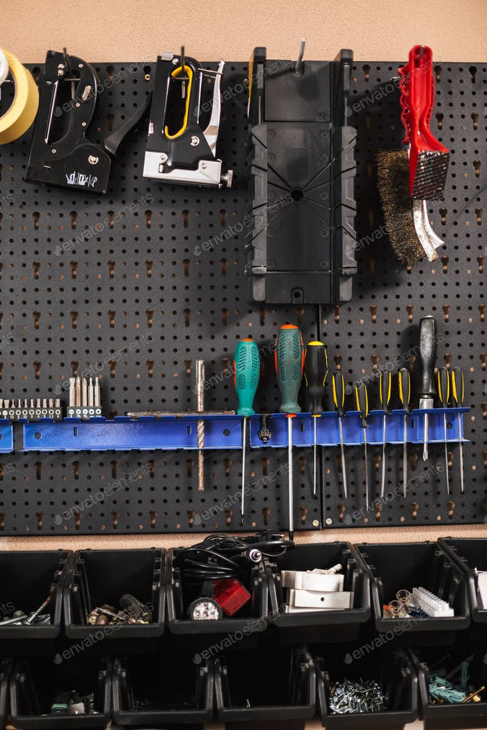 Close up stand with variety of modern tools in workshop isolated