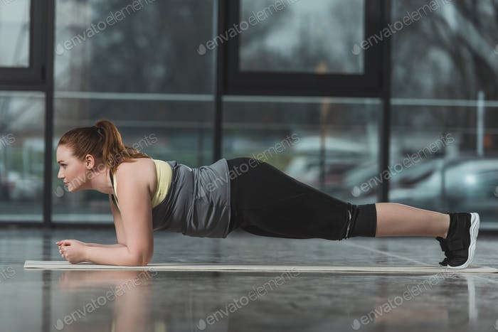 Curvy girl standing in plank in gym