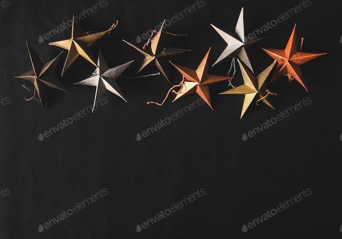 Weihnachten und Neujahr dekorative Spielzeugsterne auf schwarzem Hintergrund