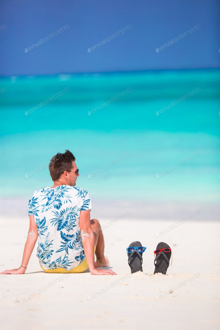 Young man enjoying time on white sandy beach at caribbean vacation
