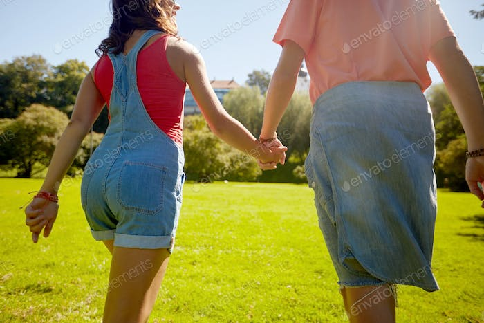 happy teenage couple walking at summer park