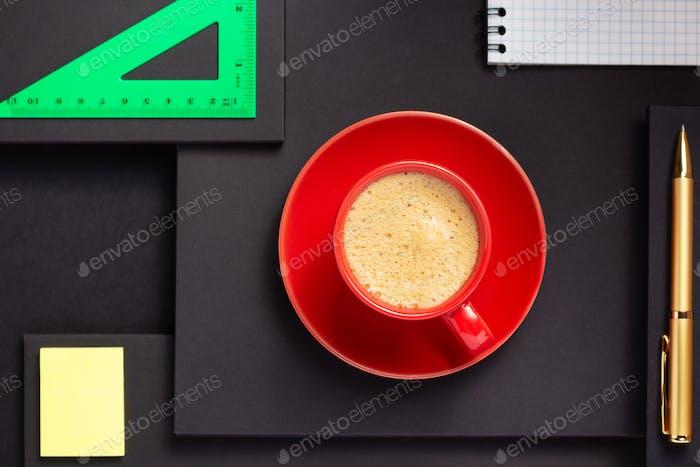 suministros de oficina y taza de café en fondo negro