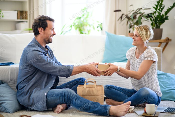 Couple sitting on floor indoors at home, food delivery service concept