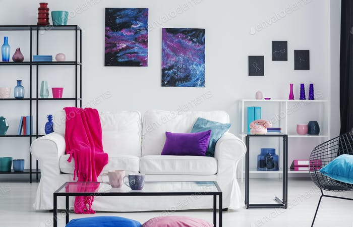 Metal shelves with vases behind white couch with pink blanket an