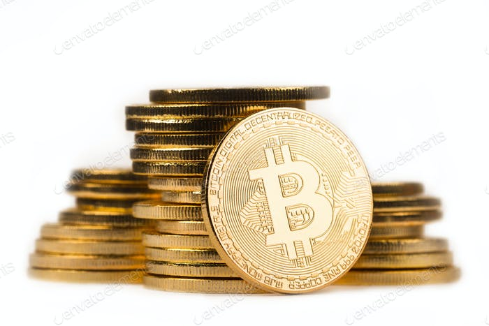 golden bitcoin in front of a pile of golden metallic coins on wh