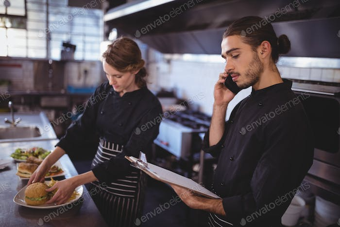 Young waiter talking on smartphone while waitress preparing food in commercial kitchen