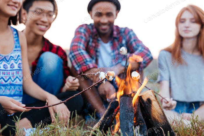 Cheerful young people talking and preparing marshmallows on bonfire outdoors