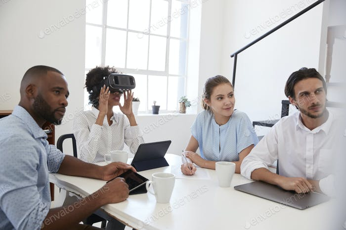 Woman in VR goggles at a desk with colleagues in an office