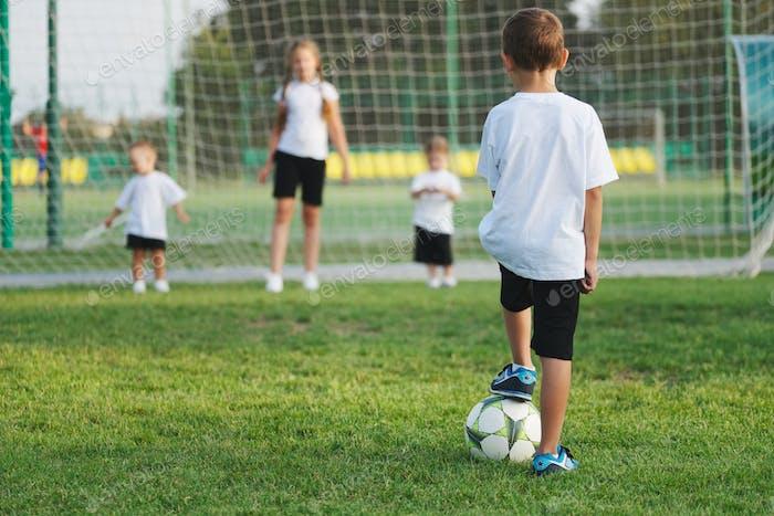 kleiner glücklicher Junge auf Fußballplatz