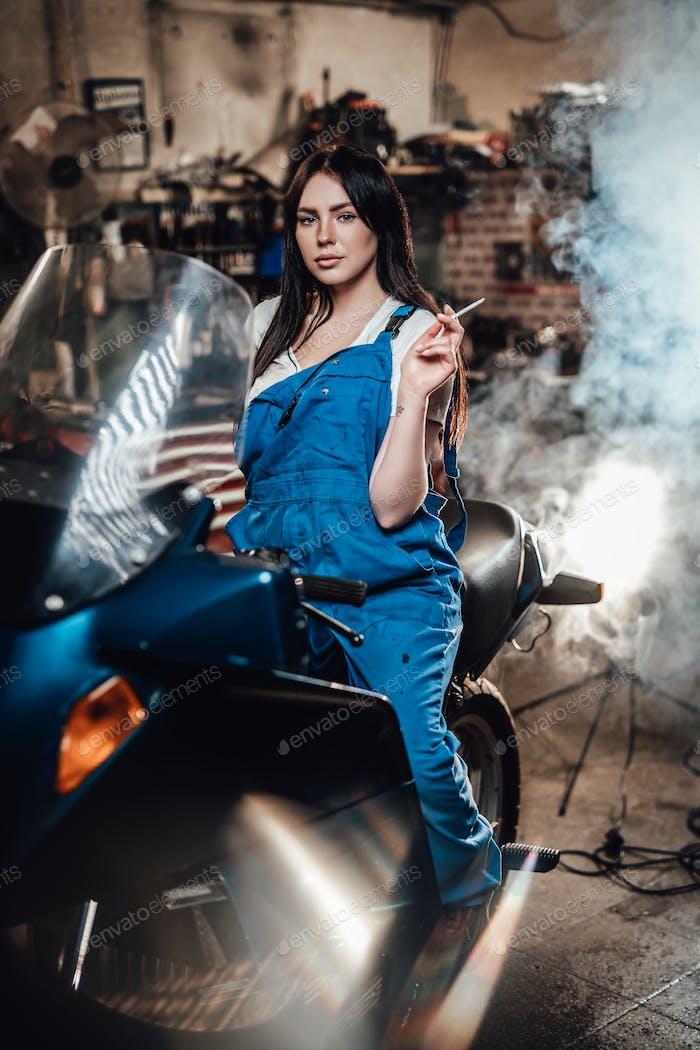 Красивая брюнетка женщина-механик в синих комбинезонах расслабляющий курить сигарету