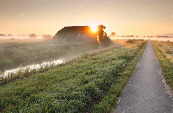 ruta ciclista por granja en el Amanecer brumoso