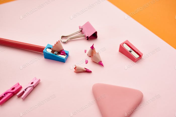 Pencil and sharpener on pink paper sheet