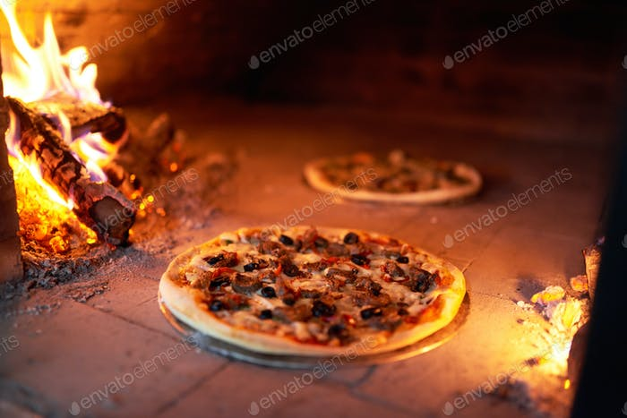 two pizzas cooked in oven with fire