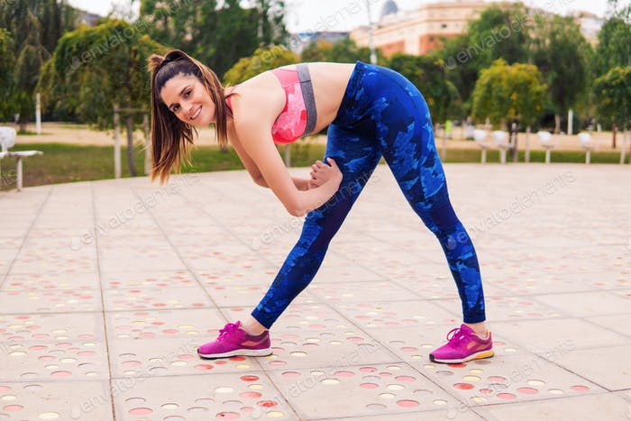 Runner fit woman warming up before sport training in the park