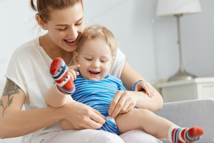 Close-up shot of happy mother and child at home. Young woman buttoning child clothes, carefully hold