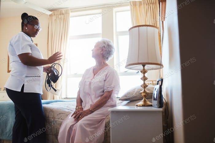 Female doctor visiting her senior patient at home
