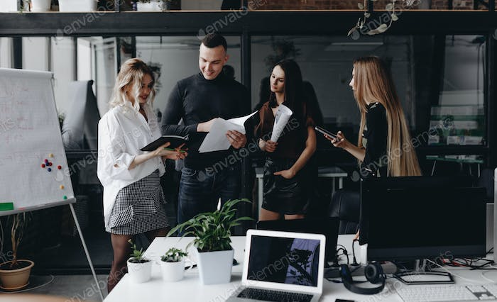 Young team works with documents and discuss the project in a stylish modern office. Work process in